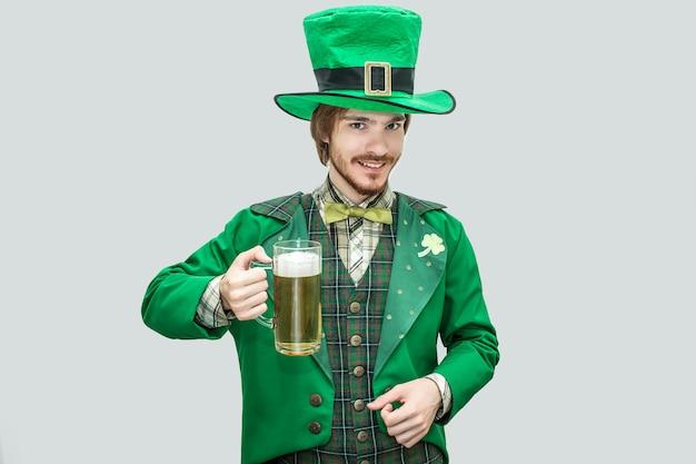 Hombre joven feliz en el traje verde de san patricio que sostiene la jarra de cerveza. él mira y sonríe. chico confiado y positivo. aislado en verde
