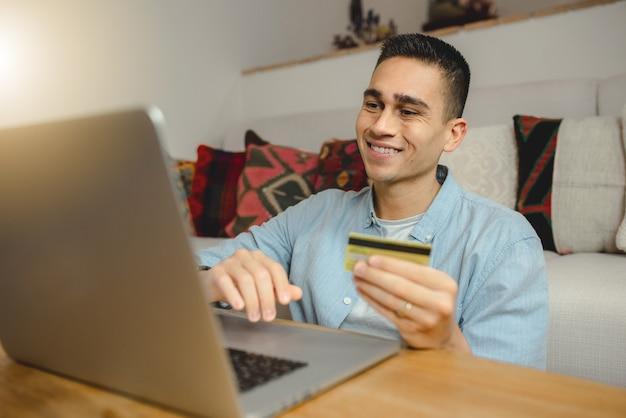 Hombre joven feliz usando la computadora portátil para compras en línea.