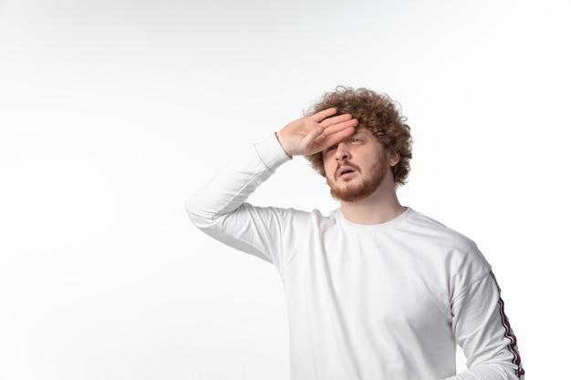 Hombre joven con fiebre en la pared blanca