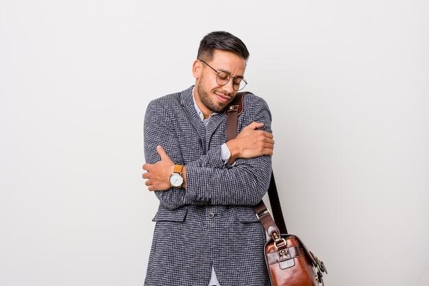 Hombre joven filipino de negocios contra una pared blanca abrazos, sonriendo despreocupado y feliz.