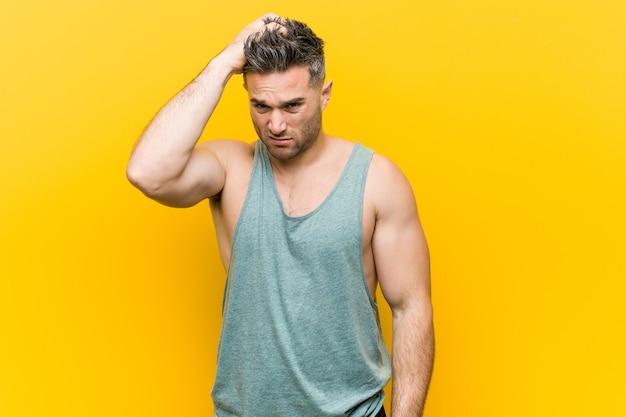 Hombre joven fitness contra un espacio amarillo cansado y con mucho sueño manteniendo la mano en la cabeza.