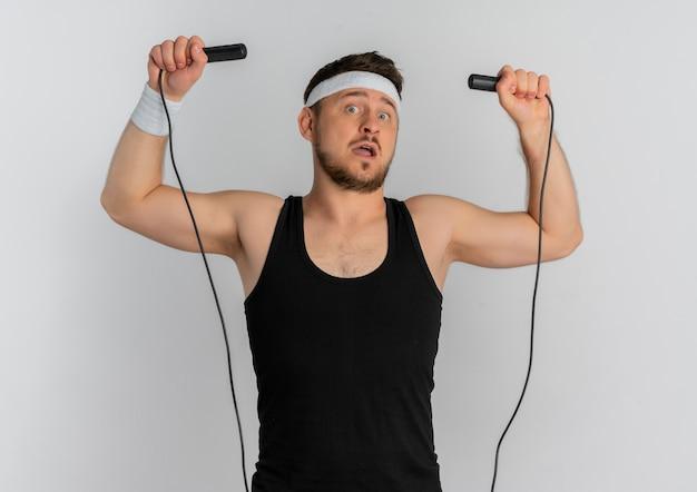 Hombre joven fitness con diadema sosteniendo saltar la cuerda va a saltar de pie sobre fondo blanco.