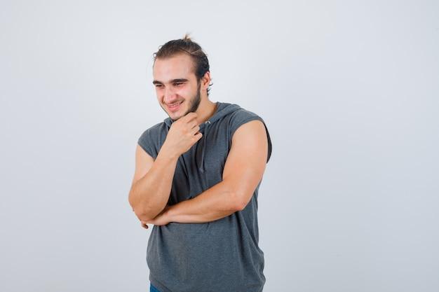 Hombre joven en forma manteniendo la mano debajo de la barbilla en una sudadera con capucha sin mangas y luciendo dichoso, vista frontal.