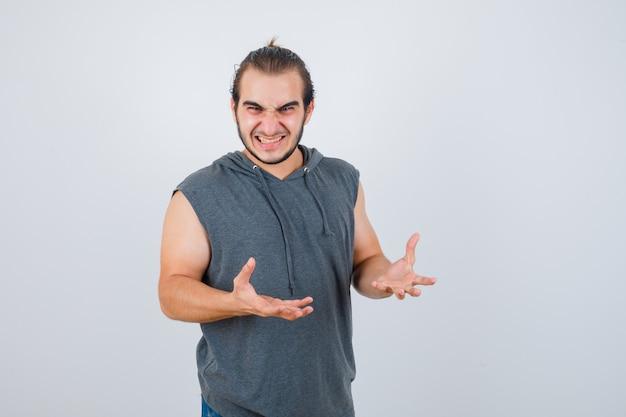 Hombre joven en forma manteniendo las manos de manera agresiva en una sudadera con capucha sin mangas y con aspecto ansioso. vista frontal.