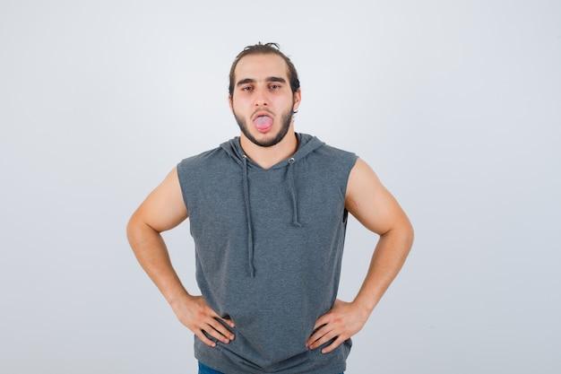 Hombre joven en forma posando con las manos en la cintura mientras saca la lengua en una sudadera con capucha sin mangas y parece disgustado. vista frontal.
