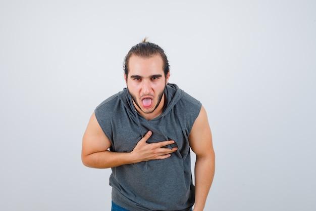 Hombre joven en forma sintiéndose con náuseas en una sudadera con capucha sin mangas y luciendo doloroso. vista frontal.
