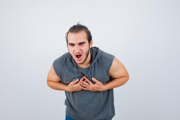 Hombre joven en forma sintiéndose con náuseas en una sudadera con capucha sin mangas y luciendo mal, vista frontal.
