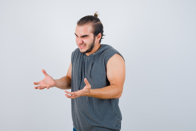 Hombre joven en forma con sudadera con capucha sin mangas, manteniendo las manos de manera agresiva y con aspecto rencoroso, vista frontal.