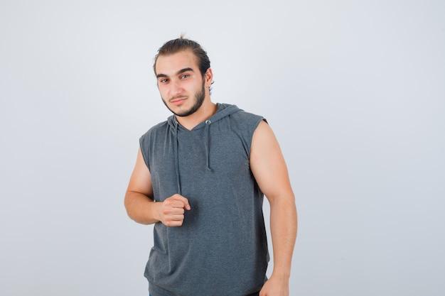 Hombre joven en forma con sudadera con capucha sin mangas que muestra el puño cerrado y parece seguro, vista frontal.