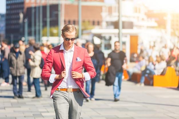 Hombre joven formado en oslo que camina en la acera llena de gente