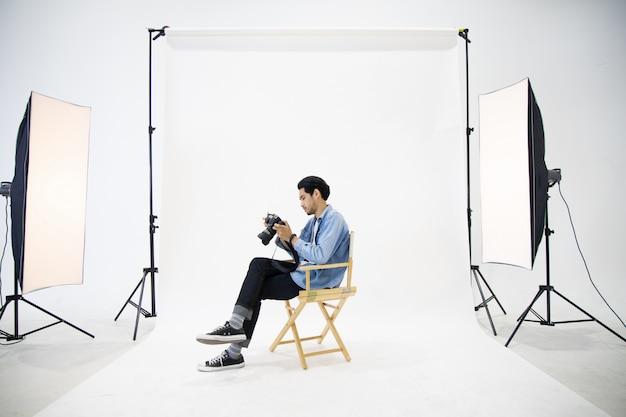 Hombre joven del fotógrafo que sienta la silla de madera y que comprueba el archivo en cámara en la escena blanca de centro en el estudio.