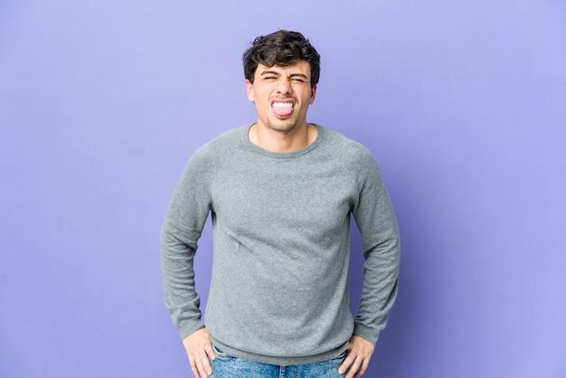 Hombre joven fresco divertido y amistoso sacando la lengua.