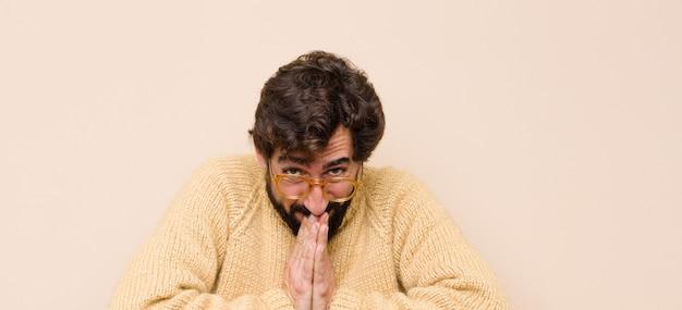 Hombre joven y fresco que se siente preocupado, esperanzado y religioso, rezando fielmente con las palmas presionadas, pidiendo perdón contra la pared plana