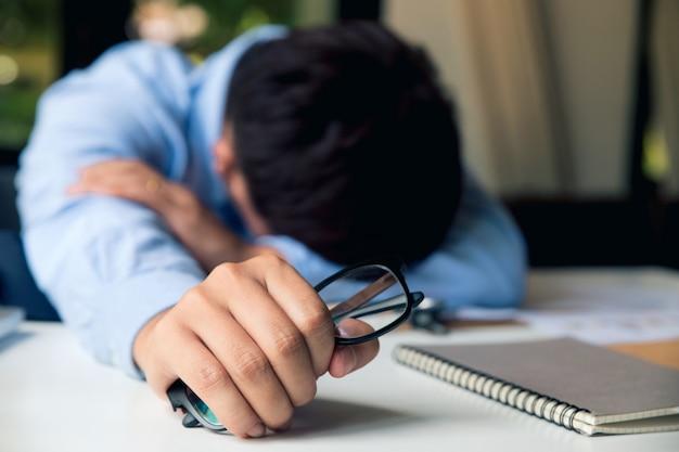 Hombre joven frustrado que parece exhausto mientras está sentado en su lugar de trabajo y llevando sus gafas en la mano.