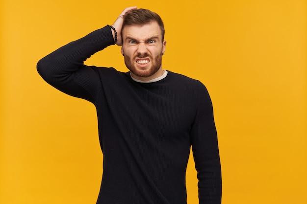Hombre joven furioso irritado con barba en manga larga negra mantiene la mano en la cabeza y se ve agresivo sobre la pared amarilla