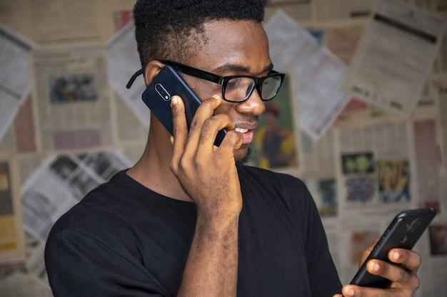 Hombre joven con gafas hablando por teléfono mientras usa otro en una habitación