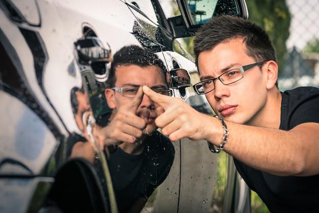 Hombre joven con gafas inspeccionando coches de lujo en el comercio de segunda mano