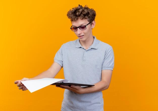 Hombre joven con gafas negras con camisa de polo gris con portapapeles con páginas en blanco mirándolo con una sonrisa en la cara sobre naranja