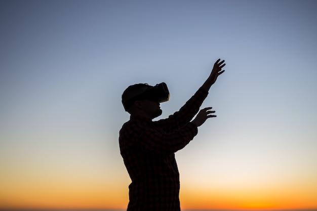 Hombre joven con gafas de realidad virtual en los sueños del cielo se hacen realidad