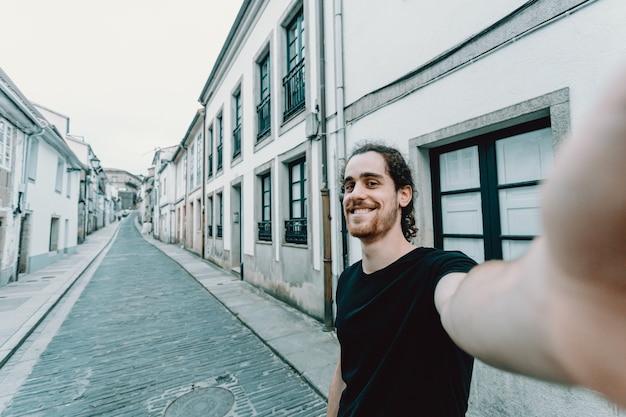 Un hombre joven con gafas tomando un selfie en una vieja calle española