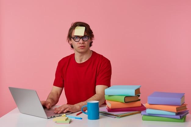 Hombre joven con gafas viste una camiseta roja, con una pegatina en la frente, se sienta junto a la mesa y trabaja con el cuaderno, preparado para el examen, con mirada seria, aislado sobre fondo rosa.