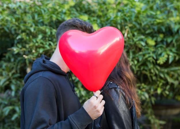 Hombre joven con globo en forma de corazón besando a mujer