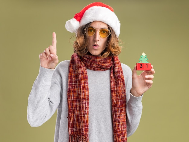 Hombre joven con gorro de navidad santa y gafas amarillas con bufanda caliente alrededor de su cuello sosteniendo cubos de juguete con fecha de año nuevo mostrando el dedo índice preocupado de pie sobre la pared verde