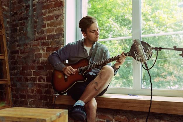 Hombre joven grabando un blog de videos musicales, una lección o una canción en casa, tocando la guitarra o haciendo un tutorial de transmisión por internet mientras está sentado en el lugar de trabajo del loft o en casa. concepto de afición, música, arte y creación.