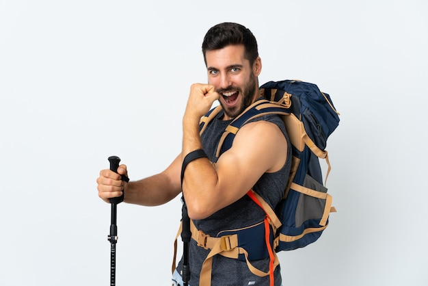 Hombre joven con una gran mochila y bastones de trekking