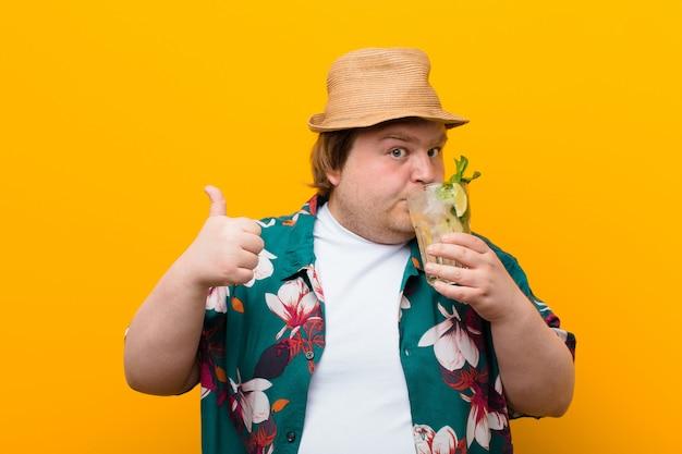 Hombre joven de gran tamaño con una bebida mojito contra la pared plana
