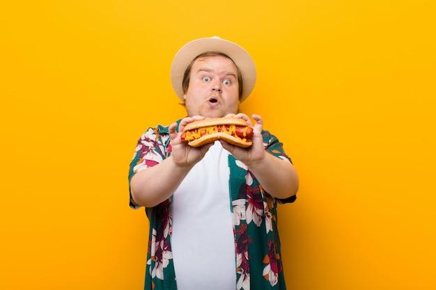 Hombre joven de gran tamaño con un hot dog contra la pared plana