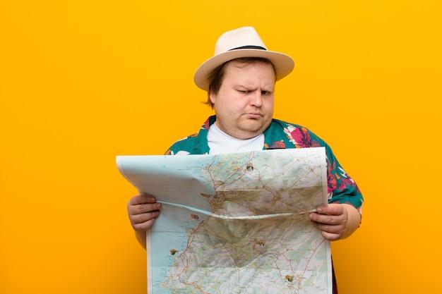 Hombre joven de gran tamaño con un mapa contra la pared plana