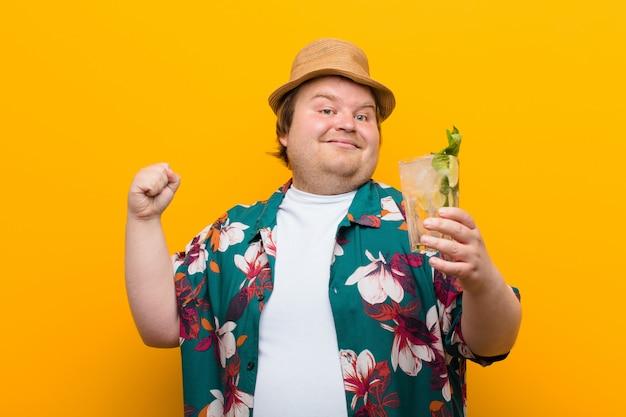 Hombre joven de gran tamaño con una pared plana de bebida mojito