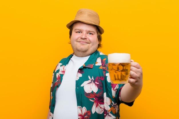 Hombre joven de gran tamaño con una pinta de cerveza contra la pared plana