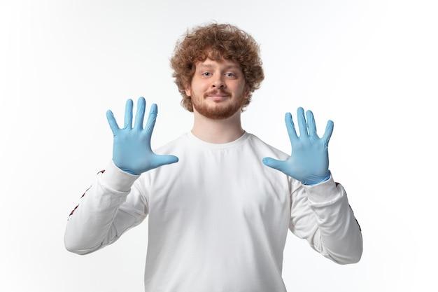 Hombre joven con guantes azules en la pared blanca