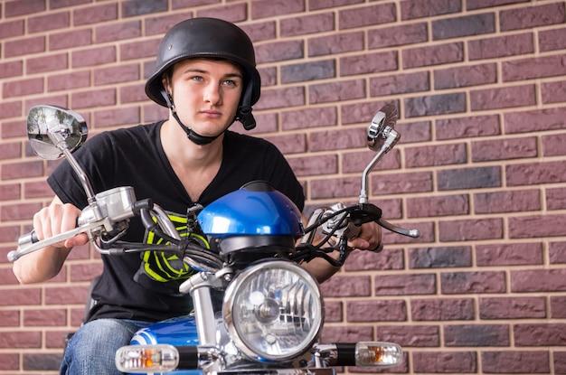 Hombre joven guapo con casco negro montando una moto en serio sobre un fondo de pared de ladrillo.