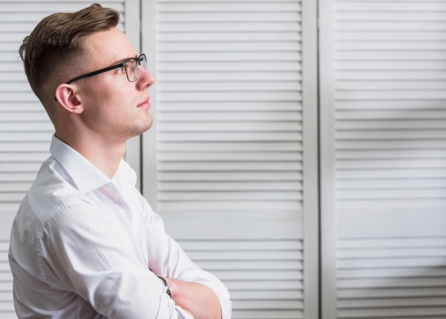 Hombre joven guapo contemplado con anteojos
