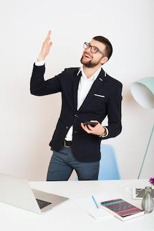 Hombre joven guapo con estilo hipster en chaqueta joven en la mesa de oficina