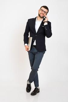 Hombre joven guapo con estilo hipster en chaqueta negra, estilo de negocios, camisa blanca, aislado, fondo blanco, sonriendo, de pie en toda su altura, mirando confiado, sosteniendo la computadora portátil, hablando por teléfono inteligente