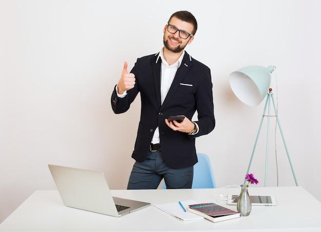 Hombre joven guapo con estilo hipster en chaqueta negra en la mesa de oficina, estilo empresarial, camisa blanca, aislado, trabajando en la computadora portátil, puesta en marcha, lugar de trabajo, sonriente, feliz, positivo,