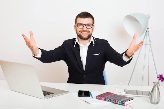 Hombre joven guapo con estilo hipster en chaqueta negra en la mesa de la oficina, estilo de negocios, camisa blanca, aislado, trabajando en la computadora portátil, puesta en marcha, lugar de trabajo, saludo de brazos abiertos, sonriente, feliz, positivo