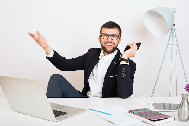 Hombre joven guapo con estilo hipster en chaqueta negra sentado en la mesa de la oficina, estilo de negocios, camisa blanca, aislado, trabajando, computadora portátil, puesta en marcha, lugar de trabajo, hablando por teléfono inteligente, sonriendo, positivo