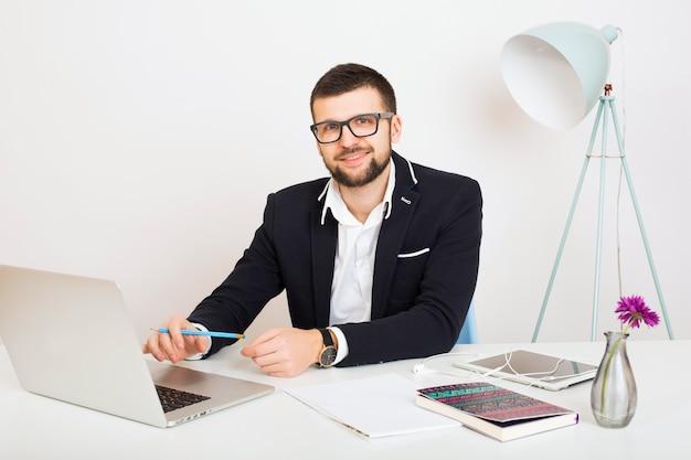 Hombre joven guapo con estilo hipster en chaqueta negra trabajando en la mesa de la oficina, estilo de negocios, camisa blanca, aislado, portátil, puesta en marcha, lugar de trabajo, lápiz, hojas de papel, ocupado