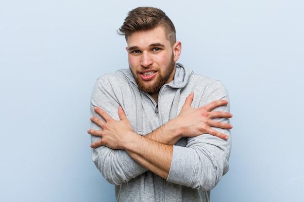 Hombre joven guapo fitness frío debido a la baja temperatura o una enfermedad.