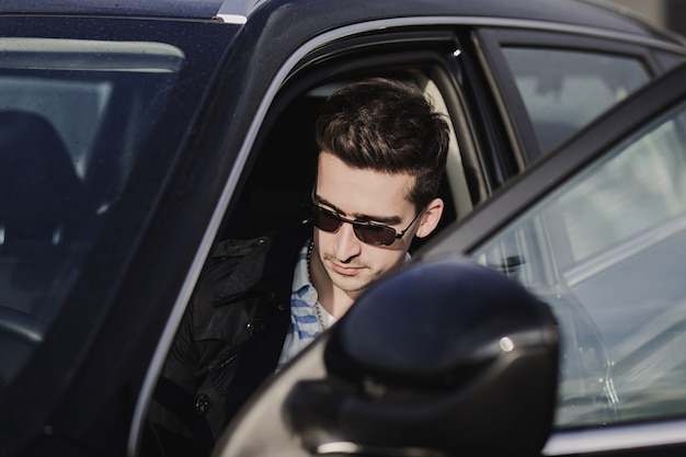 Hombre joven guapo con gafas conduciendo coche moderno