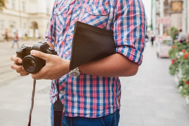 Hombre joven guapo hipster caminando con cámara de fotos en la calle de la ciudad vieja