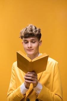 Hombre joven y guapo leyendo un libro en un escenario amarillo