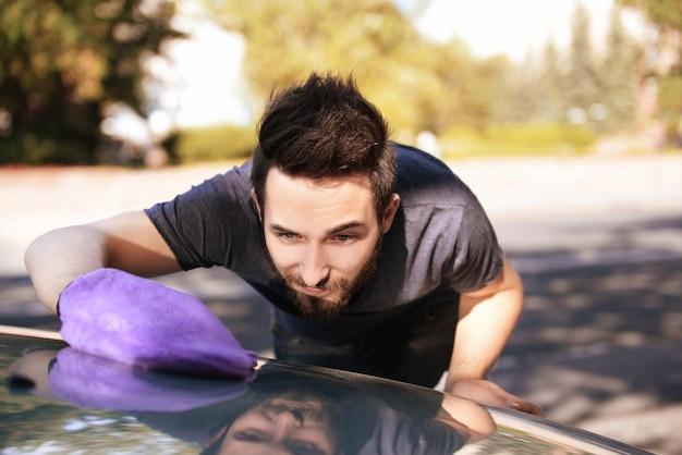 Hombre joven guapo limpiando el coche con un guante especial