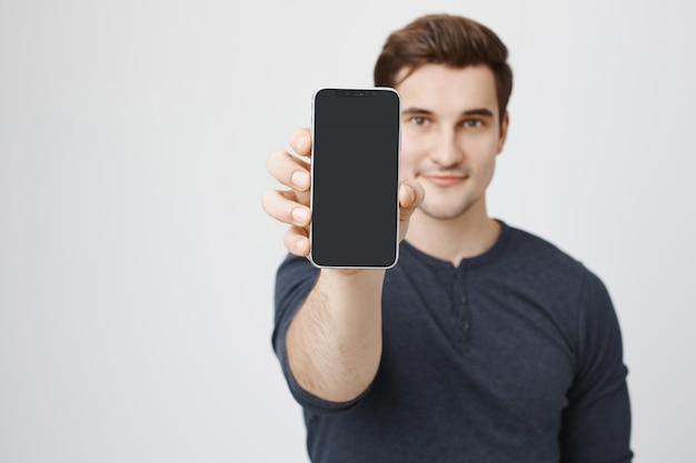 Hombre joven guapo mostrando la pantalla del teléfono móvil