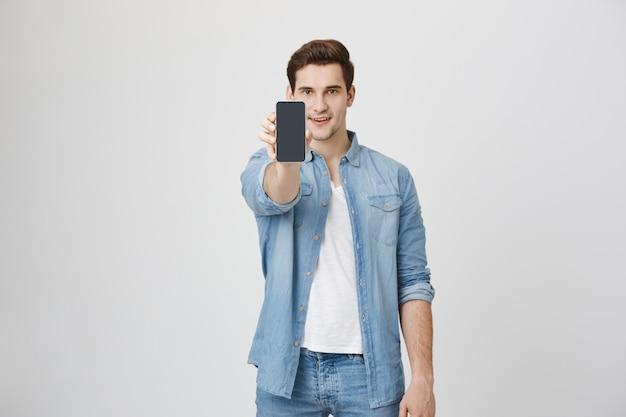 Hombre joven guapo mostrando smartphone